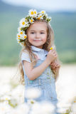 Little girl in a wreath of white daisies Stock Photo