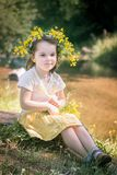 little girl in a wreath of yellow flowers Stock Photo