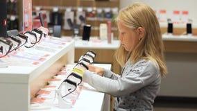 Little girl in a wristwatch store. Smart watch.  stock footage