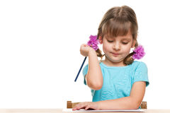 Little girl writes at the desk Stock Image