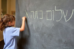 Little girl writes Hello First Grade greetings in Hebrew. Little girl (Age 5-6) writes Hello First Grade greetings in Hebrew (Shalom Kita Alef) on a chalkboard stock photo