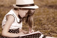 Little girl writes in her notebook Stock Photo