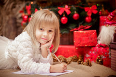 Little girl writes a letter to Santa Claus. Near Christmas tree Royalty Free Stock Photo