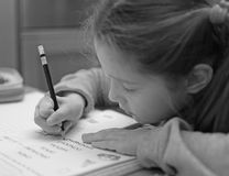 Little girl writes on the notebook of schoolwork Royalty Free Stock Photography