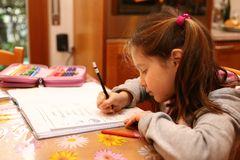 Little girl writes on the notebook of schoolwork Royalty Free Stock Photos