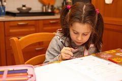 Little girl writes with pencil on book school exercises Stock Photos