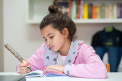 Little girl writes on the school diary. Girl writes in the diary school homework with a wooden pencil Royalty Free Stock Images