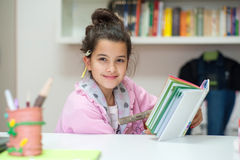 Little girl writes on the school diary. Girl writes in the diary school homework with a wooden pencil Stock Photo
