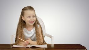 Little girl writes to writing-book on white background. Close up. Professional shot in 4K resolution. 095. You can use it e.g. in your commercial video stock images