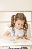 Little girl writing alphabet in a copy book at the desk Stock Image