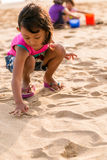 Little girl writing on the beach sand Stock Photos