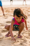 Little girl writing on the beach sand Royalty Free Stock Photos