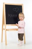 Little girl writing on a blackboard. Little girl with chalk in her hands standing near blackboard. Isolating on white Royalty Free Stock Image
