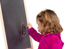 Little girl writing on a blackboard. A Little girl writing on a blackboard Royalty Free Stock Image