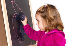 Little girl writing on a blackboard Stock Images