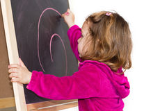 Little girl writing on a blackboard Stock Photo