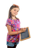 A little girl writing on a blackboard with chalk Royalty Free Stock Photos