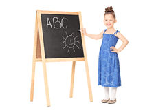 Little girl writing on a blackboard. Full length portrait of a little girl writing on a blackboard isolated on white background Royalty Free Stock Photo