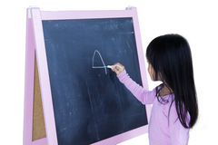 Little girl writing on blackboard. Little girl writing number on the blackboard with a chalk, isolated on white background Royalty Free Stock Photography