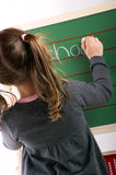 Little girl is writing on a board Royalty Free Stock Photos