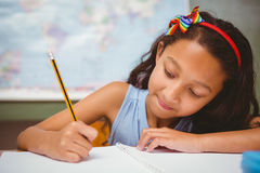 Little girl writing book in classroom Stock Images