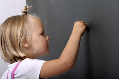 Little girl writing on a chalk board Royalty Free Stock Image