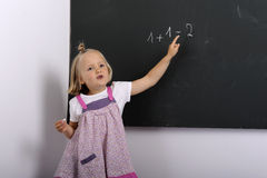 Little girl writing on a chalkboard Stock Photo