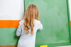 Little Girl Writing On Chalkboard In Classroom Stock Image
