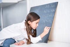 Little girl writing chemical formula Stock Photos