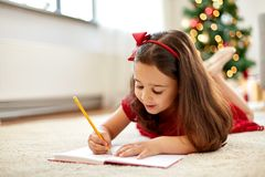 Little girl writing christmas wish list at home Royalty Free Stock Image