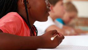 Little girl writing during class. In elementary school stock footage