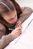 Little girl writing concentrated on her exercise book Stock Images