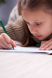 Little girl writing concentrated on her exercise book Royalty Free Stock Images
