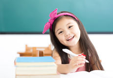 Little girl writing at desk in classroom Stock Photo