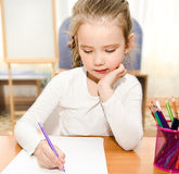 Little girl is writing at the desk  in preschool Royalty Free Stock Photo