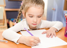Little girl is writing at the desk  in preschool. Cute little girl is writing at the desk  in preschool Royalty Free Stock Photography