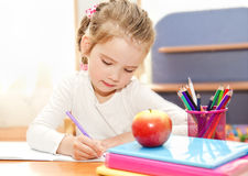 Little girl is writing at the desk  in preschool Stock Photography