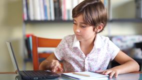 Little girl doing homeworks with a laptop and a notebook. stock footage