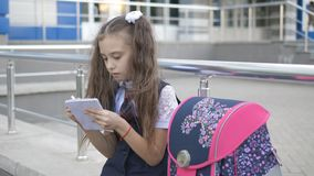 Girl in school uniform near school building after school writes something in a notebook. stock footage