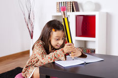 Little girl writing with a giant pencil Stock Images