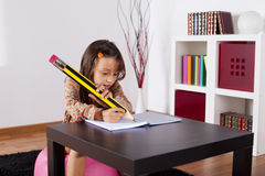 Little girl writing with a giant pencil Royalty Free Stock Photo