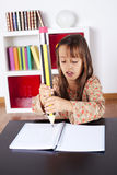 Little girl writing with a giant pencil stock image