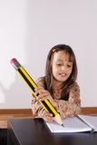 Little girl writing with a giant pencil Royalty Free Stock Photos