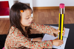 Little girl writing with a giant pencil Royalty Free Stock Images