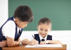 Little girl writing homework in classroom Stock Images