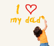 Little girl writing I Love my dad with  brush Royalty Free Stock Photo