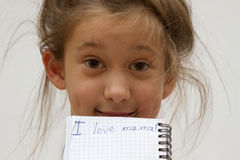 Little girl writing I Love my mom. Cute happy little girl writing something in her notebook fun Stock Photos