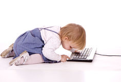 Little girl writing on keyboard of computer Stock Photos
