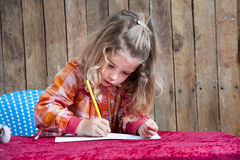 Little girl writing a letter Stock Photos