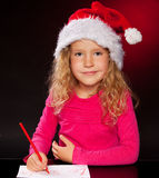 Little girl writing a letter to Santa Claus Royalty Free Stock Image
